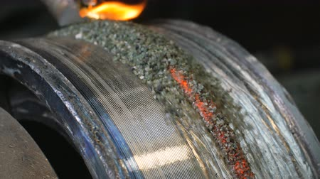 resistência : Close up of welding robots apply overlay weld protection on the pipe disks. Automatic welding of pipe-rolling