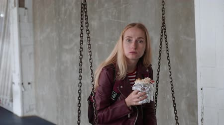 donner : Woman eats, fast food, doner kebab, pita, shawarma. Swing in a seesaw. Loft place Stock Footage