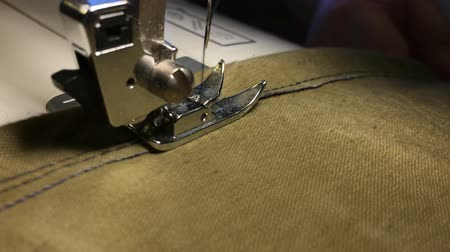 рукоделие : Fabrics on the sewing machine. Scribbles the thread on the rough fabric.