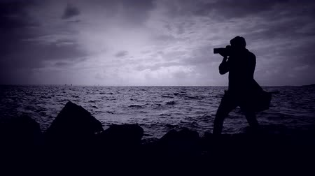 Photographer on shooting a seascape. Enthusiastic creative person with a camera. To capture nature in photographs. Turbulent seas and a photographer in the wind. Stock Footage