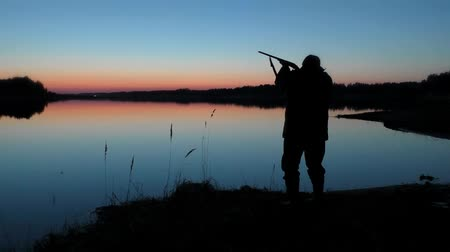 single shot : Hunter with a gun waiting for a duck at sunset by the lake.