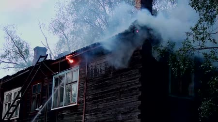 Burning old wooden house with stove heating. The tragedy of the fire dwelling.