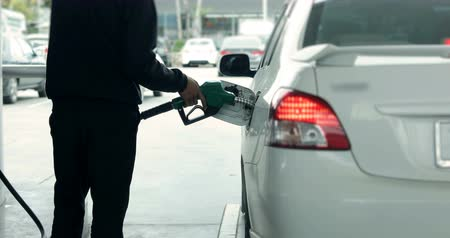 worker using the fuel nozzle supply pumping oil to car at the gas station 動画素材