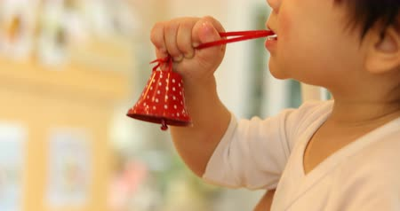 cute baby playing small red bell in christmas day