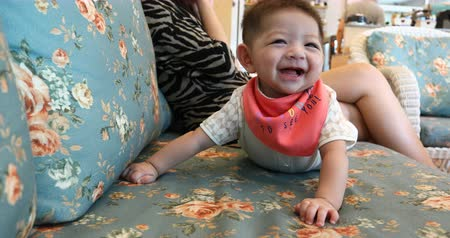 baby boy happy smile cheerful on sofa furniture with mother talking mobile phone in cafe coffee 動画素材