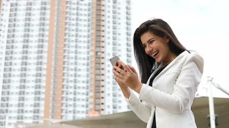 happy businesswoman watching mobile phone face time live surprise have a good news of business