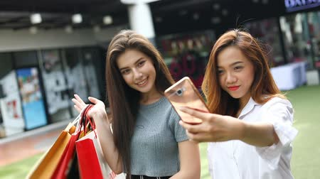 feliz : two asian women friendly selfie take a photo happy time in lifestyle shopping mall Stock Footage