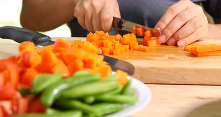 chef cooking food sliced carrot with knife on wooden chopping board Стоковые видеозаписи