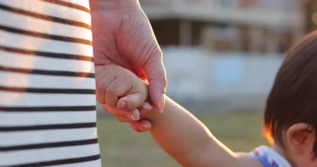 mother holding hand baby son with beautiful light of sunset, feeling love family life concept scene