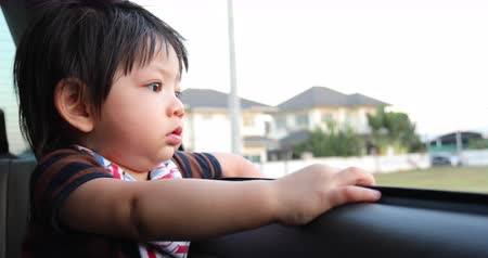 auta : baby boy looking out of window car driving from house