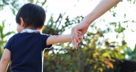 infantil : child boy holding hand mother walking naughty in the park Stock Footage