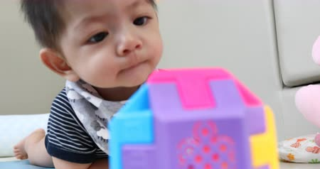 tentar : cute asian baby boy playing ball toy on soft mattress floor in nursery room