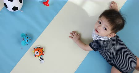 denemek : baby boy crawl playing on soft mattress floor in nursery room