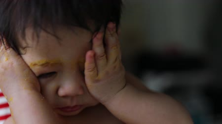 emmek : cute baby boy using finger hand in mouth itchy gum with food puree dirty on face, child sleepy