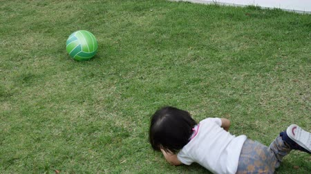 volleyball : slow-motion, funny child running falling on green grass turf playground