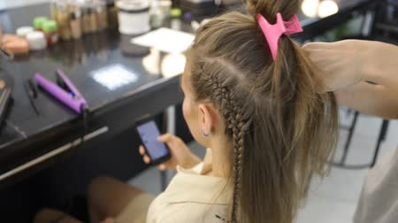 supermodel : Girl uses smart phone in Hairdressers while hairdresser work on clients hair