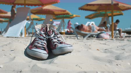 spor ayakkabısı : Red sneakers at the beach, vacationers people background