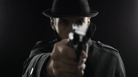 ameaça : Portrait of a gangster in a hat and a black cloak threatens weapon Stock Footage