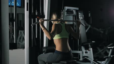 zdůraznit : Athletic girl do Wide-Grip Pulldown Behind The Neck in a gym