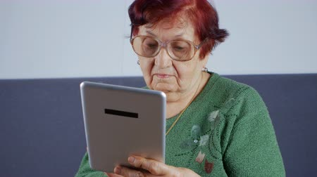 memórias : Close up of an old woman and electronic tablet.