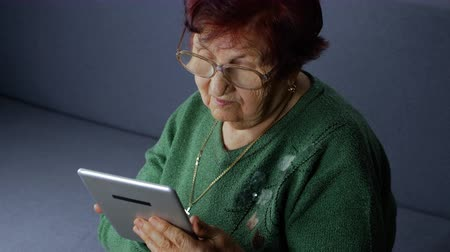 stary : Lonely grandmother using tablet computer, she looking pictures