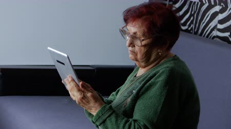 memórias : Lonely grandmother using tablet computer, she looking pictures