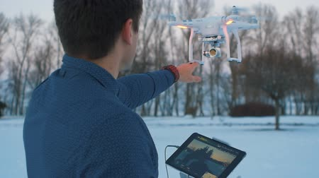 stable fly : A man controls a drone at winter garden. He touches his hand quadrocopter Stock Footage