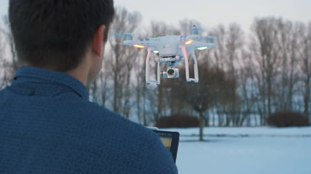stable fly : People and robots. Guy controls a drope. Man touches drone quadrocopter
