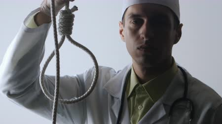 prescribe : The doctor offers a choice between a noose and a medicine. The choice between suicide or treatment. Stock Footage