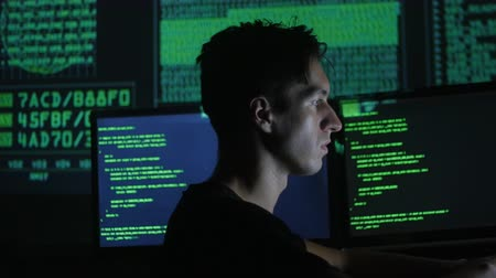 kódolás : portrait of a young programmer working at a computer in the data center filled with display screens