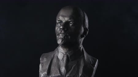 ulyanov : A rotating bust of Vladimir Lenin on a black background in smoke. History of the USSR and the commune era.