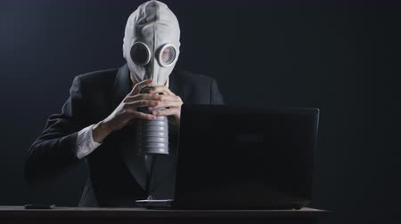 терроризм : Businessman wearing gas mask working at laptop in dark office