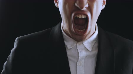 řvát : aggressive businessman in a suit is screaming and showing anger on a black background. Angry boss. The danger of violence