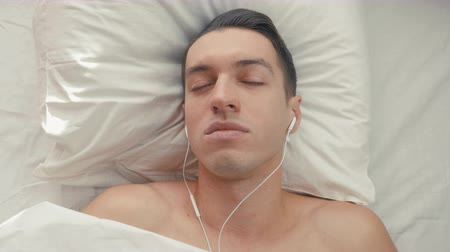 пробуждение : young man lies in bed on pillows and listens to music on headphones using smartphone