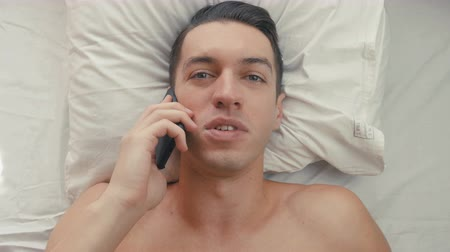 пробуждение : close-up of a young man talking on a mobile phone lying in bed in the morning. The begining of the work day
