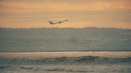 aeroespaço : plane takes off over the waves of the ocean at sunset in slow motion