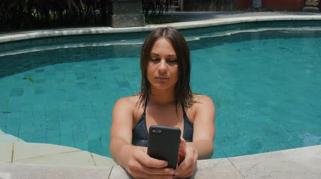devise : young woman uses a smartphone by the side of a pool.
