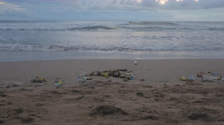 feiúra : Time-lapse of a lot of trash and plastic wastes on ocean beach after the storm. Kuta, Bali, Indonesia.