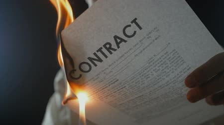 povinnost : Close-up of a man burns a contract document. Destruction of securities. Interruption of an agreement Dostupné videozáznamy