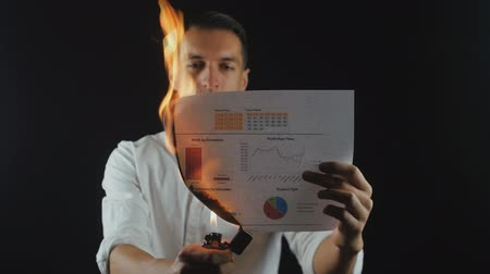 povinnost : businessman burns paper schedule of financial sales. Dostupné videozáznamy