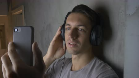 Young man with headphones listening music with smartphone