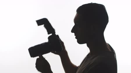 Photographer Silhouette close-up. Young man takes pictures with DSLR camera isolated on white background