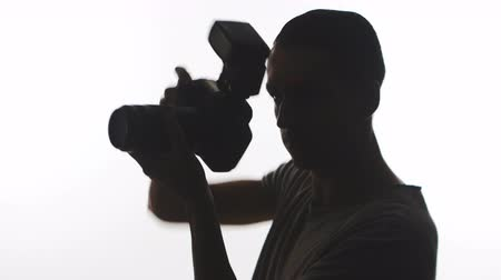 Silhouette of Photographer close-up. Young man takes pictures with DSLR camera isolated on white background