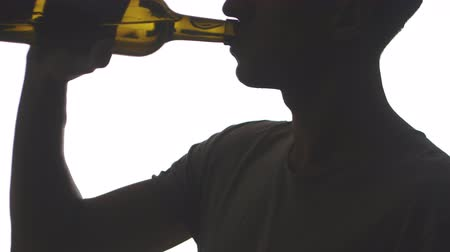 close up of silhouette man drinks alcohol a bottle. Young man drinks wine isolated on white background