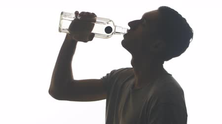 silhouette of a drunk man drinking vodka from a bottle isolated on white background