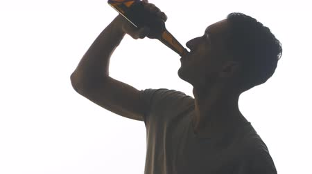 silhouette of a young man drinking beer from a bottle isolated on white background