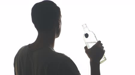 silhouette of a drunk man drinking vodka from the throat of a bottle isolated on white background
