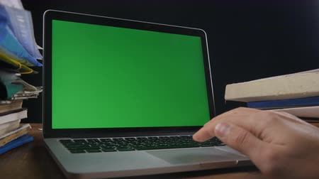 előléptetés : Close up of man works at laptop late ot office with Green Screen. Businessman working at night at the computer with Choma Key. Stock mozgókép