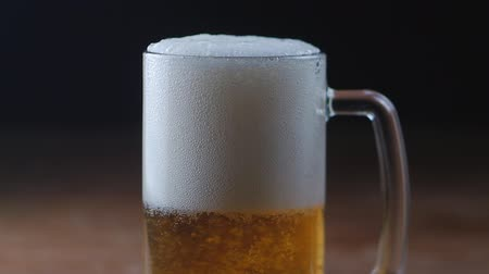 Cold Light Beer in a glass with black background, slow motion Dostupné videozáznamy