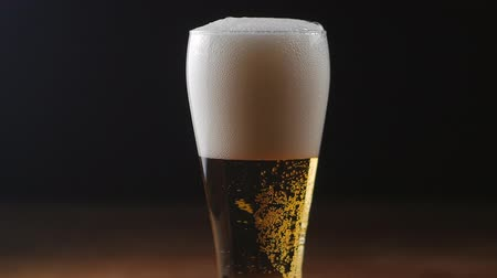 Beer is pouring into glass on black background. Slow motion Dostupné videozáznamy